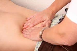 The doctor palpates the patient's abdomen